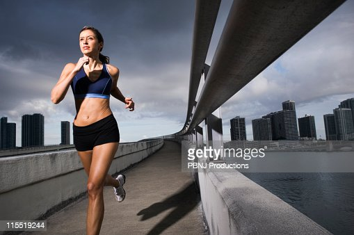 Hispanic woman running near urban waterfront : Stock Photo