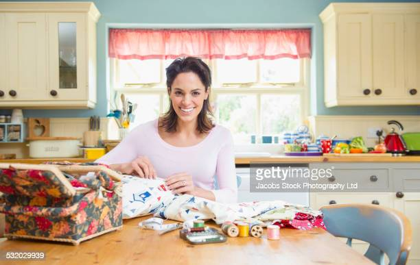 Hispanic woman sewing at kitchen table