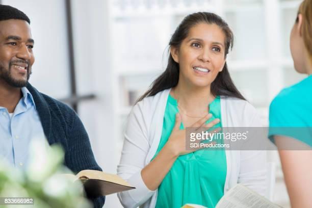 Hispanic woman shares during office Bible study