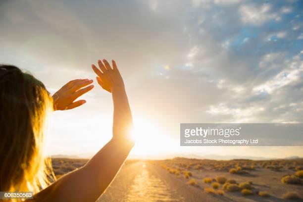 Hispanic woman shielding eyes from sun on remote road