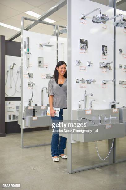 Hispanic woman shopping for bathroom fixture in store