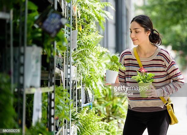 Hispanic woman shopping for plants in nursery