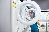 Hispanic woman shopping for washing machine in store