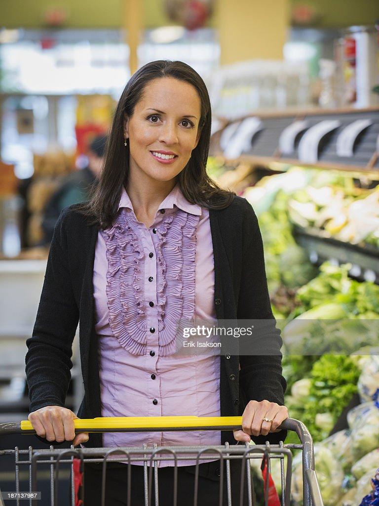 Hispanic woman shopping in grocery store : Stock Photo