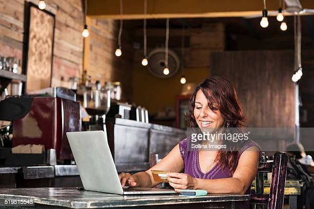 Hispanic woman shopping on laptop in coffee shop