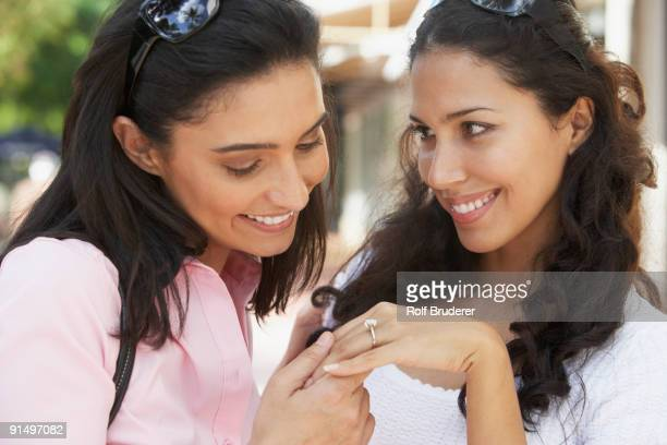 Hispanic woman showing engagement ring to friend