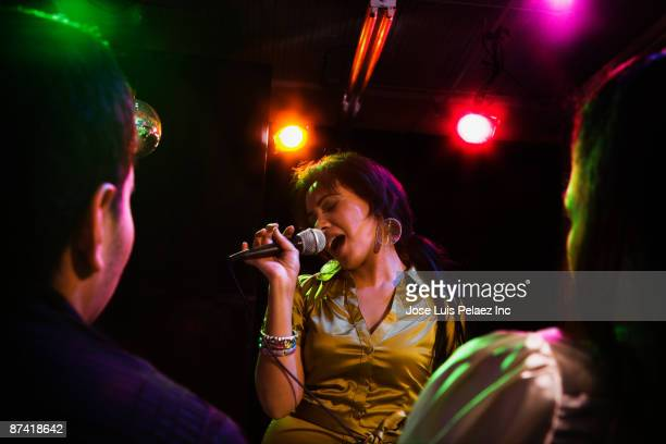 Hispanic woman singing in nightclub