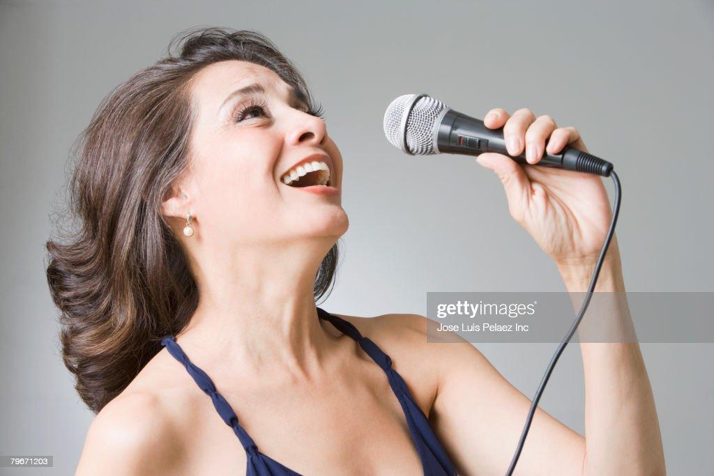 Hispanic woman singing into microphone : Stock Photo
