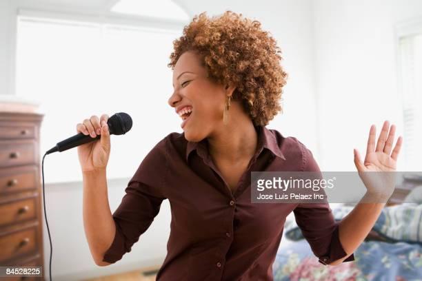 Hispanic woman singing on microphone in bedroom