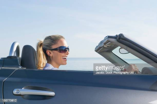 Hispanic woman sitting in car looking at ocean