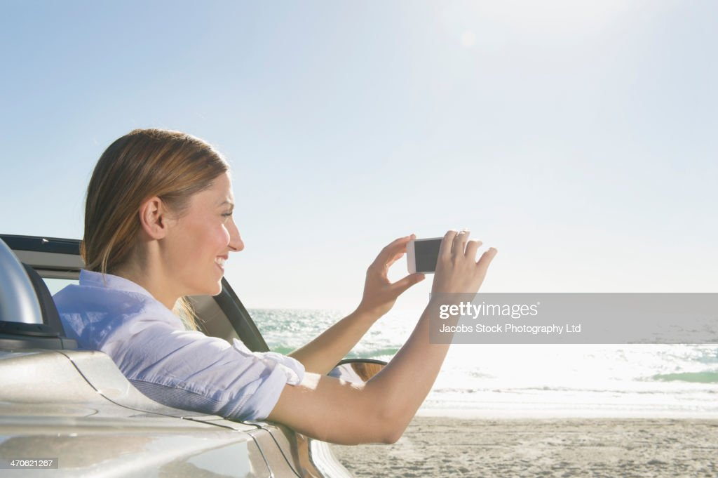 Hispanic woman sitting in convertible on beach : Stock Photo