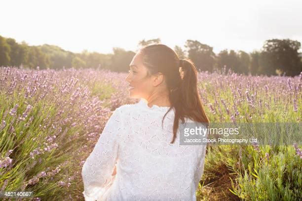 Hispanic woman sitting in lavender field
