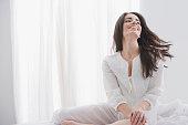 Hispanic woman sitting on bed smiling