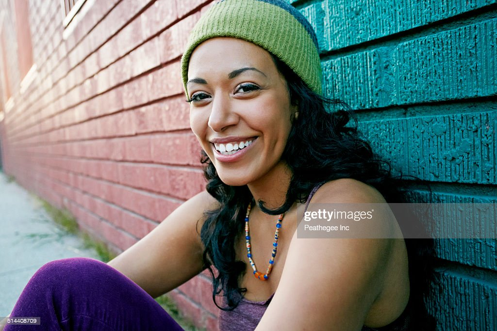 Hispanic woman sitting on city street
