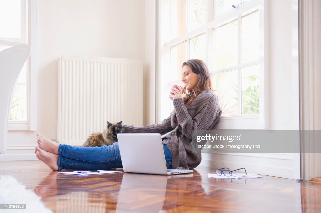 Hispanic woman sitting on floor with laptop and cat : Stock Photo