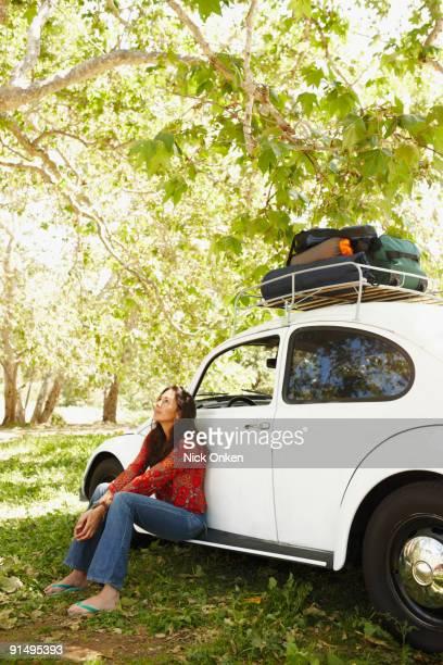 Hispanic woman sitting on side of car