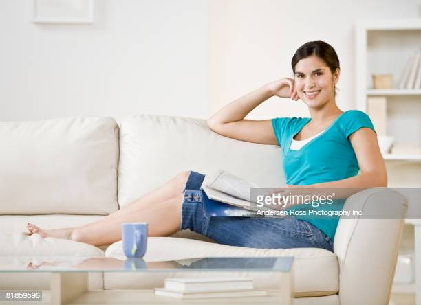 Hispanic woman sitting on sofa