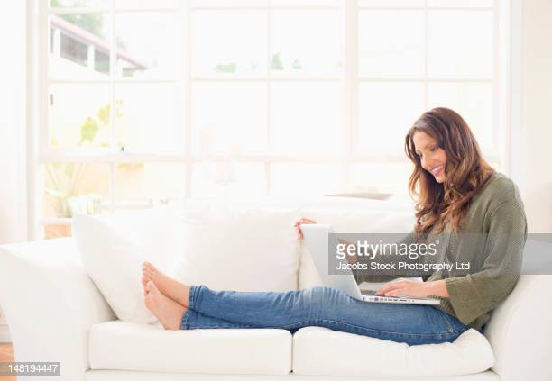 Hispanic woman sitting on sofa using laptop