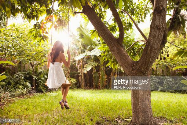 Hispanic woman sitting on tree swing