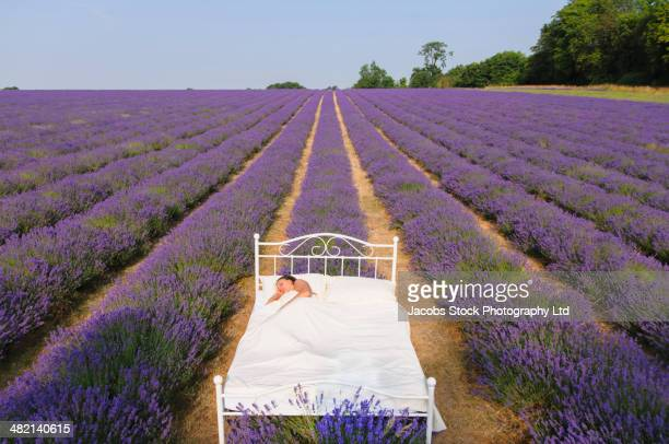 Hispanic woman sleeping in bed in lavender field