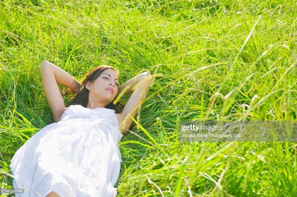 Hispanic woman sleeping in grass : Stock Photo