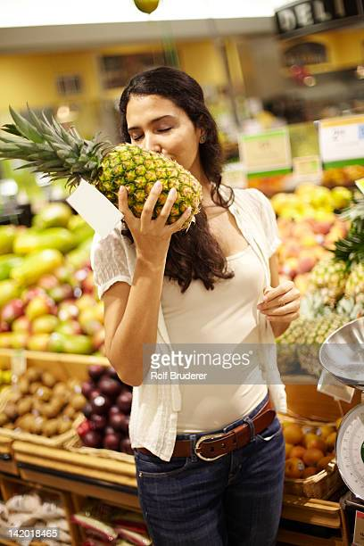Hispanic woman smelling pineapple in grocery store