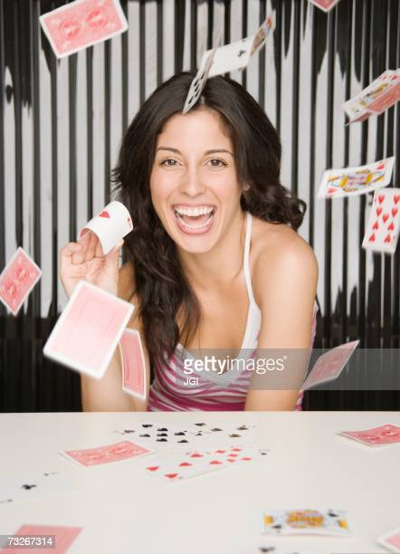 Hispanic woman smiling and throwing playing cards
