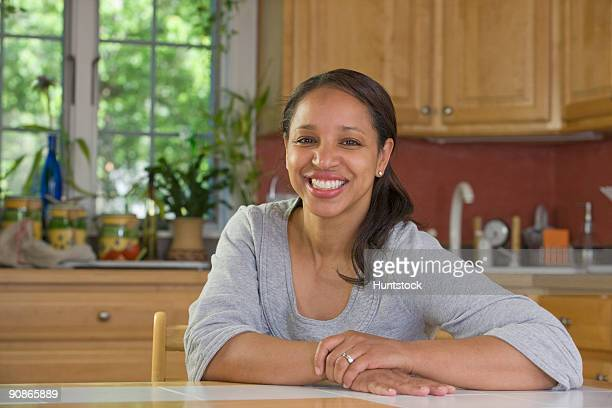 Hispanic woman smiling at a dining table