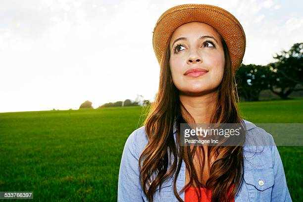 Hispanic woman smiling in grassy field