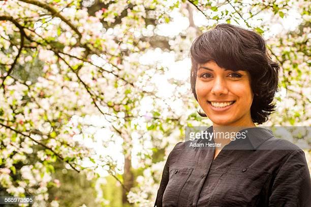 Hispanic woman smiling under trees