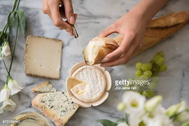 Hispanic woman spreading cheese on bread
