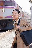 Hispanic woman standing at a railway station
