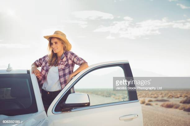 Hispanic woman standing in car on remote road