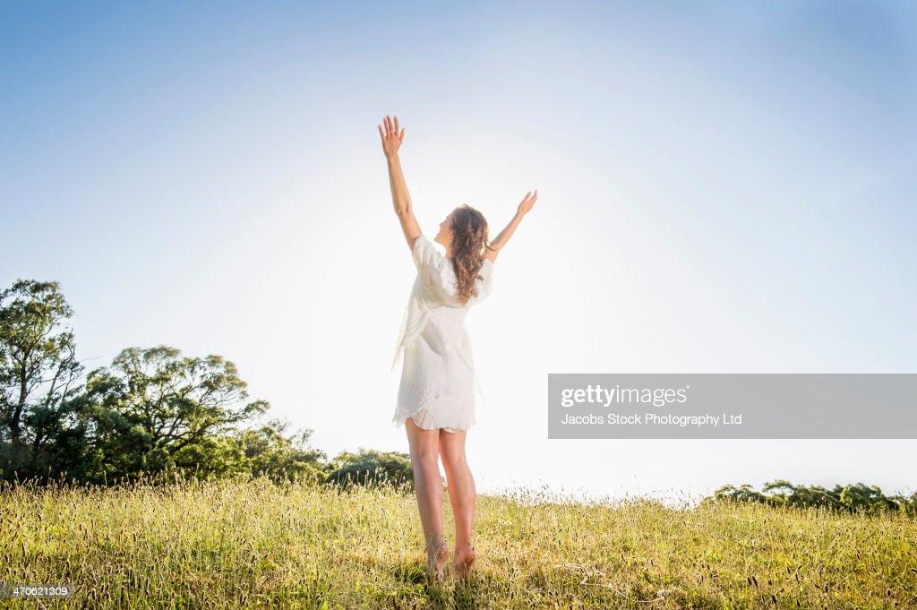 Hispanic woman standing in grass