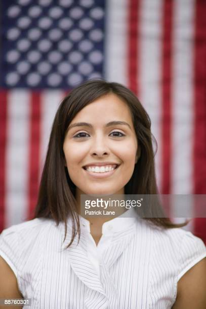 Hispanic woman standing near American flag