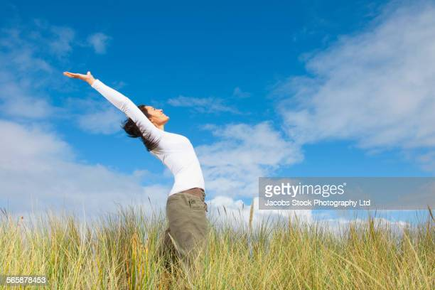 Hispanic woman stretching in tall grass field
