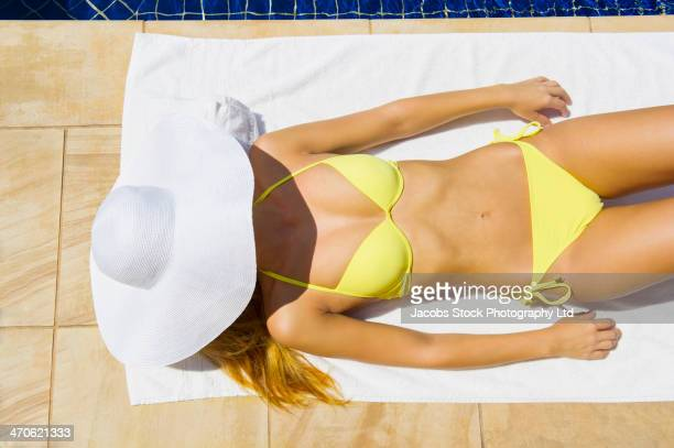 Hispanic woman sunbathing by pool