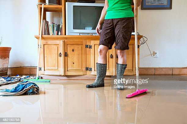 Hispanic woman sweeping water out of flooded house