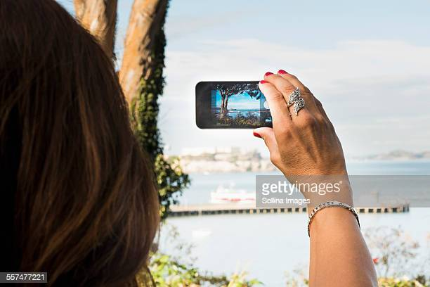 Hispanic woman taking cell phone photograph of beach