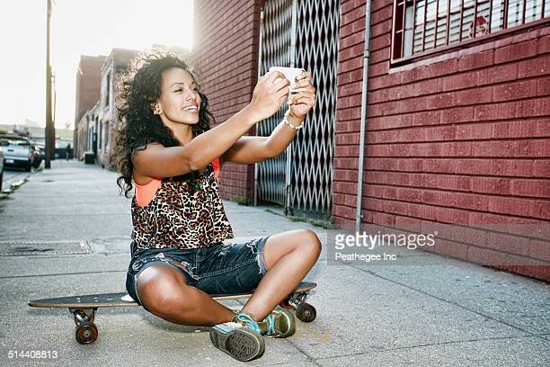 Hispanic woman taking cell phone picture on skateboard on city street