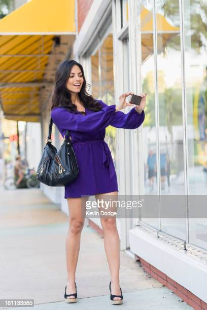 Hispanic woman taking photograph of store window