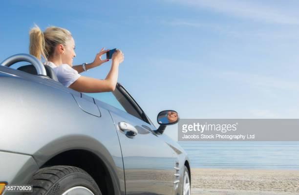 Hispanic woman taking photographs of ocean