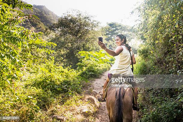 Hispanic woman taking pictures on horseback in jungle