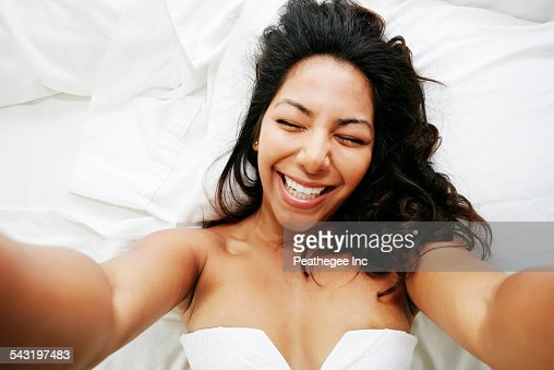 Hispanic woman taking selfie of herself on bed