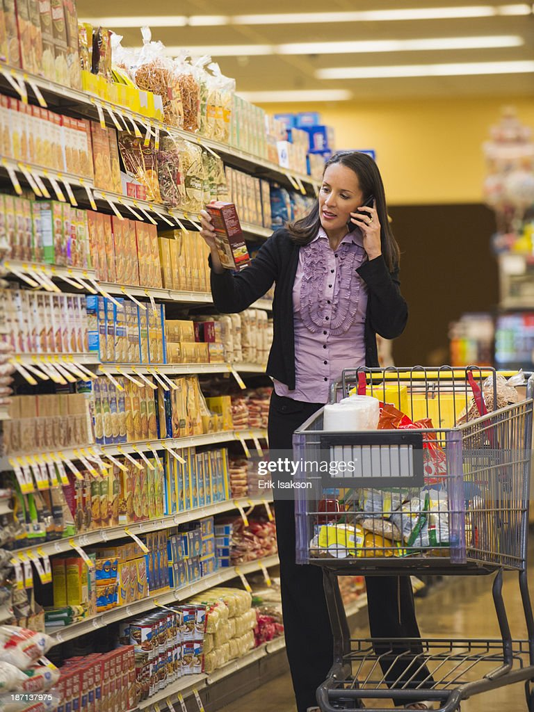 Hispanic woman talking on cell phone in grocery store : Stock Photo