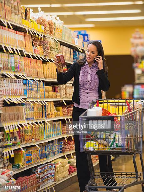 Hispanic woman talking on cell phone in grocery store