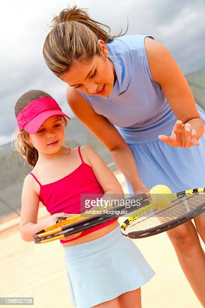 Hispanic woman teaching girl to play tennis