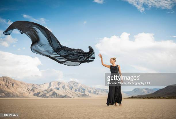 Hispanic woman tossing scarf in remote desert