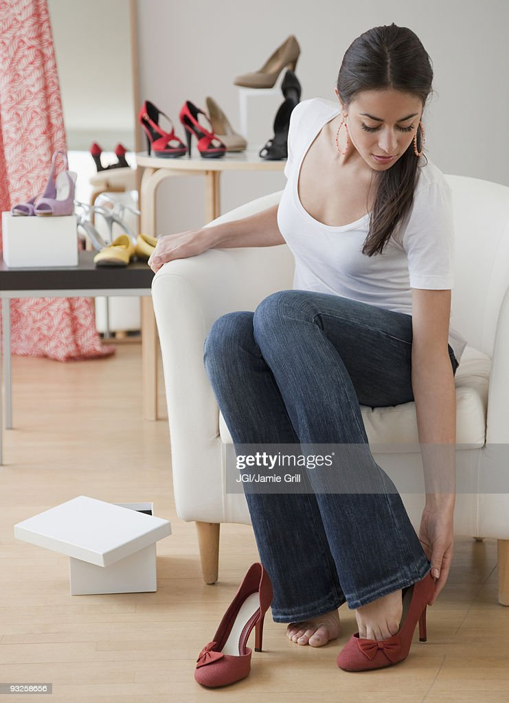 Hispanic woman trying on high heels at store