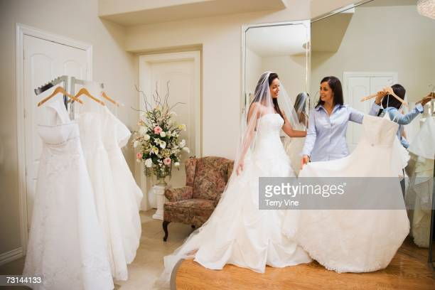 Hispanic woman trying on wedding dresses